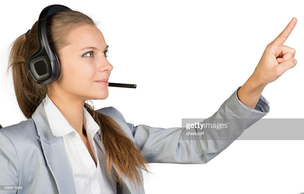 Empresaria en auriculares tocar o presionando algo : Foto de stock