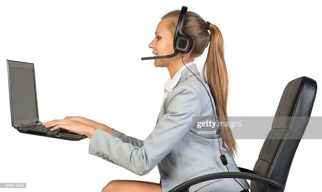 Businesswoman in headset, typing on laptop keyboard : Stock Photo