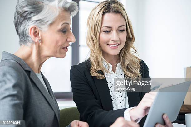 Businesswoman in her 30s using tablet with mature colleague