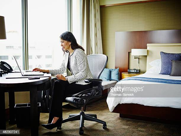 Businesswoman in hotel room working on laptop