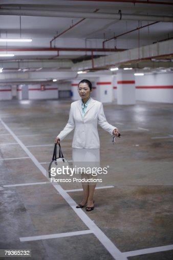 Businesswoman in indoor parking garage looking for her car : Stock Photo