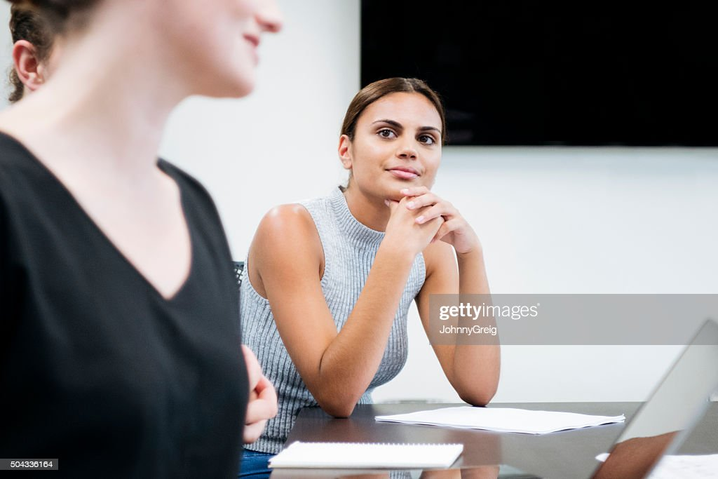 Businesswoman in meeting listening to colleague, hands on chin : Stock Photo