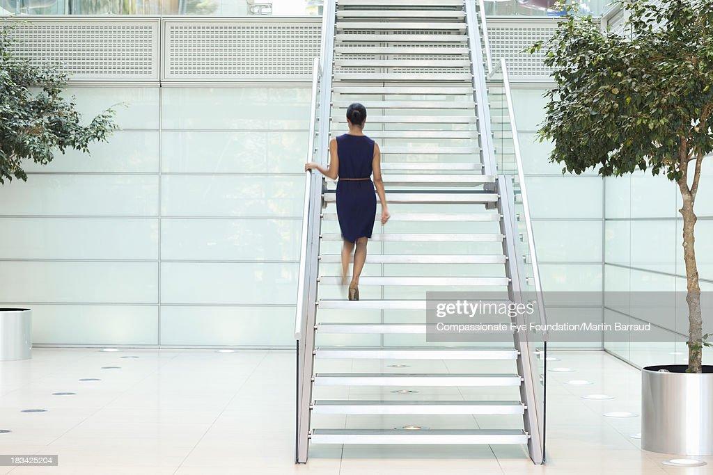 Businesswoman in modern lobby, rear view