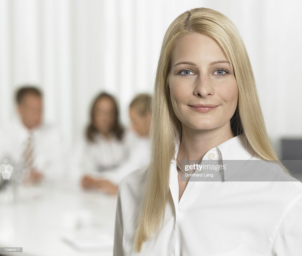 Businesswoman in office, smiling, businesspeople in background, portrait, close-up : Stock Photo