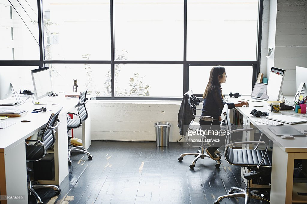 Businesswoman in office working on computer : Stock Photo
