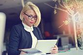 Businesswoman in office working on digital tablet.