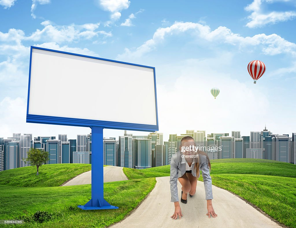 Businesswoman in running start pose on the road : Stock Photo