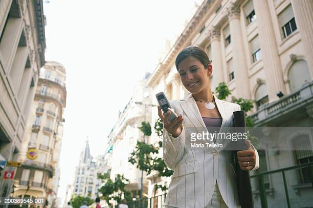 Businesswoman in street using mobile phone, smiling, low angle view