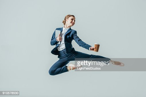 businesswoman in suit and ballet shoes jumping with coffee and digital tablet : Stock Photo