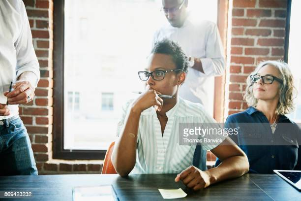 Businesswoman in team meeting with colleagues in office conference room