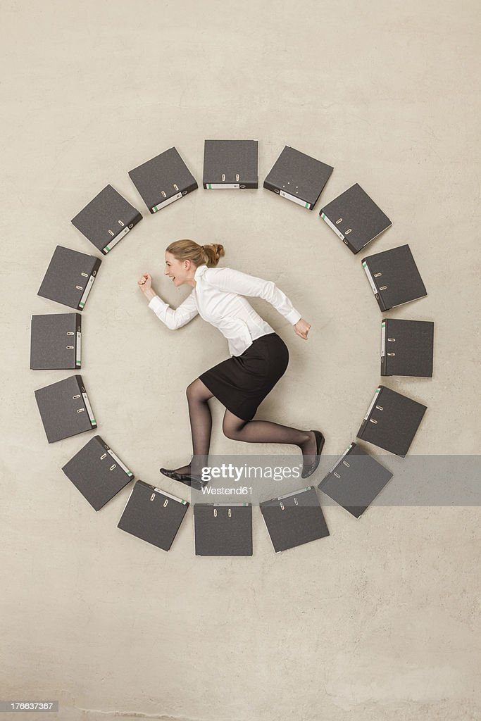 Businesswoman inside circle of files forming clock