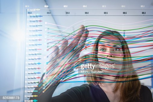Businesswoman inspecting graph on interactive display