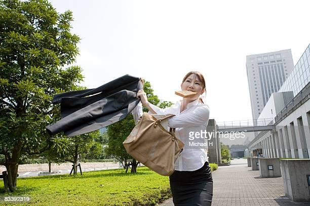 Businesswoman is biting bread and walking