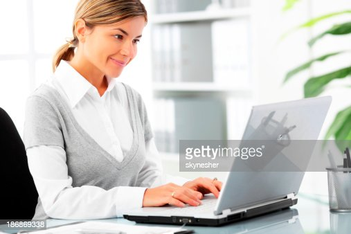 Businesswoman is typing on laptop.