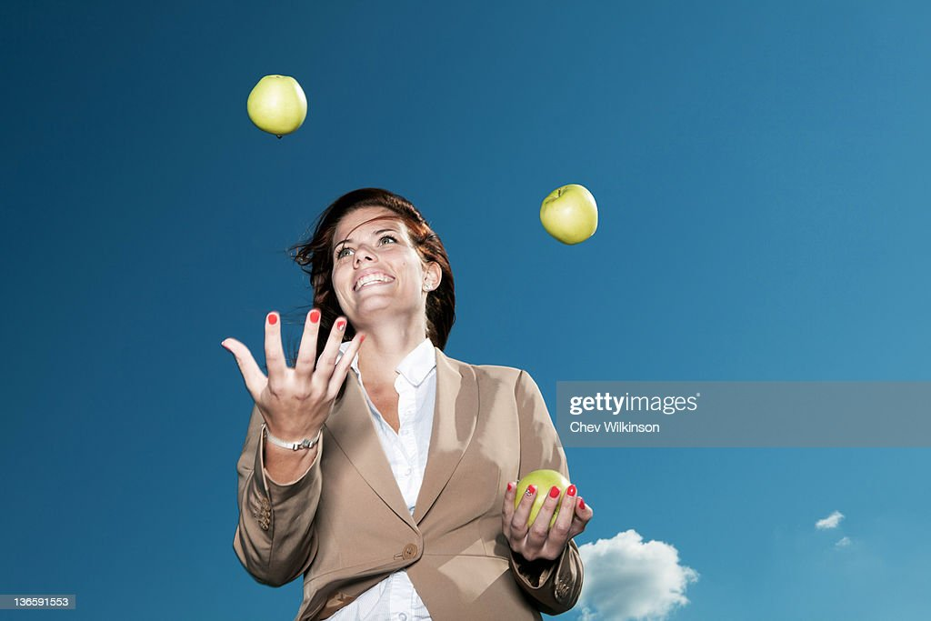 Businesswoman juggling apples outdoors : Stock Photo