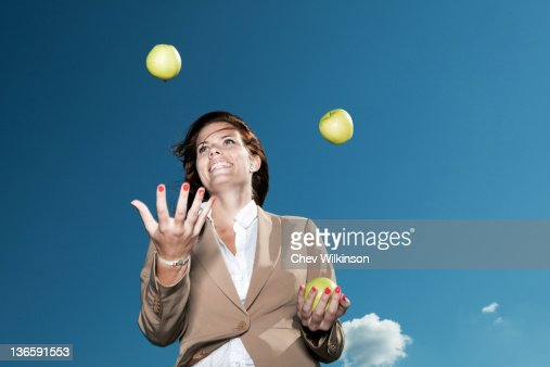 Businesswoman juggling apples outdoors : Stock-Foto
