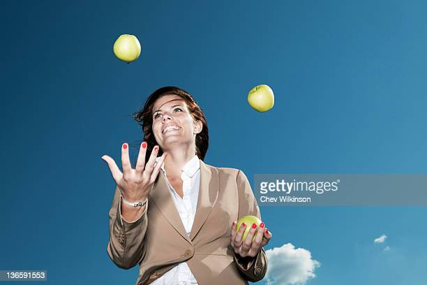 Businesswoman juggling apples outdoors