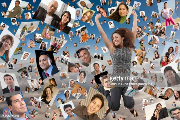 Businesswoman jumping for joy in images of faces floating in sky