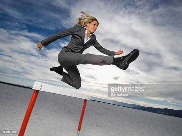 Businesswoman jumping over hurdle, Salt Flats, Utah, United States