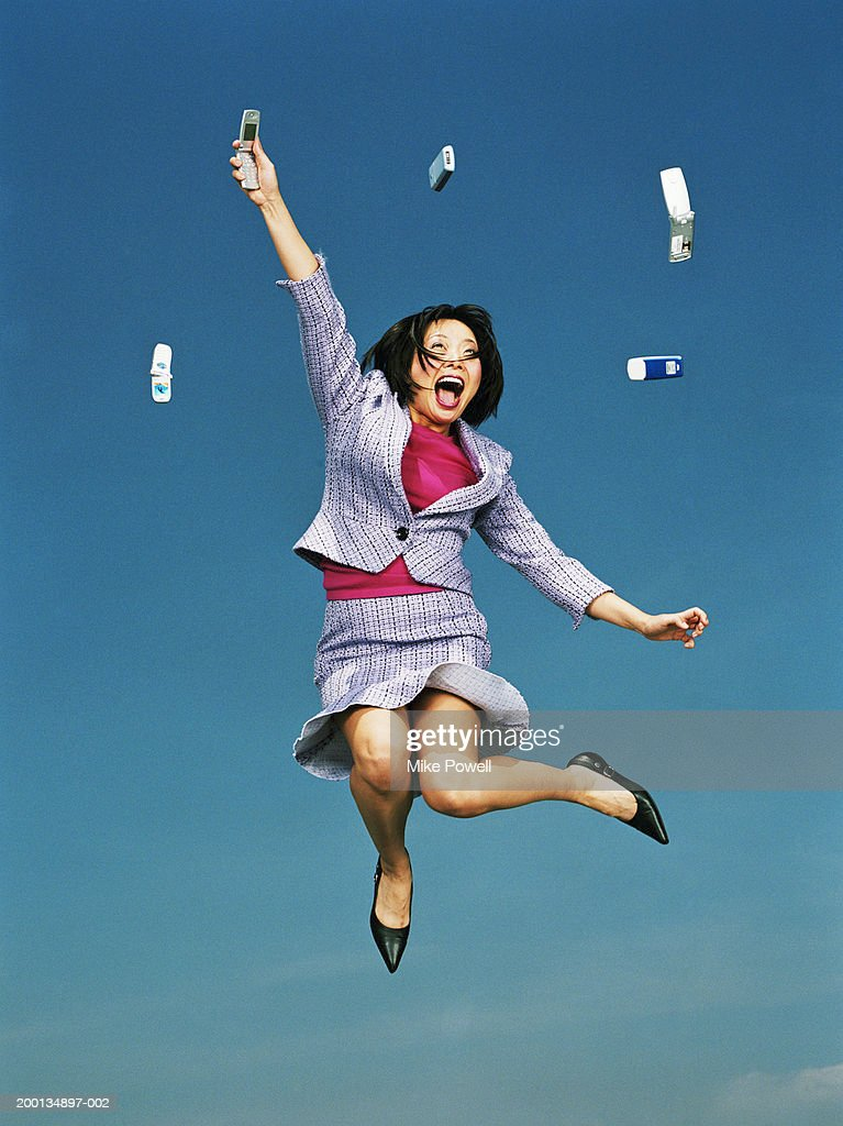 Businesswoman jumping with mobile phones in air, low angle : Stock Photo