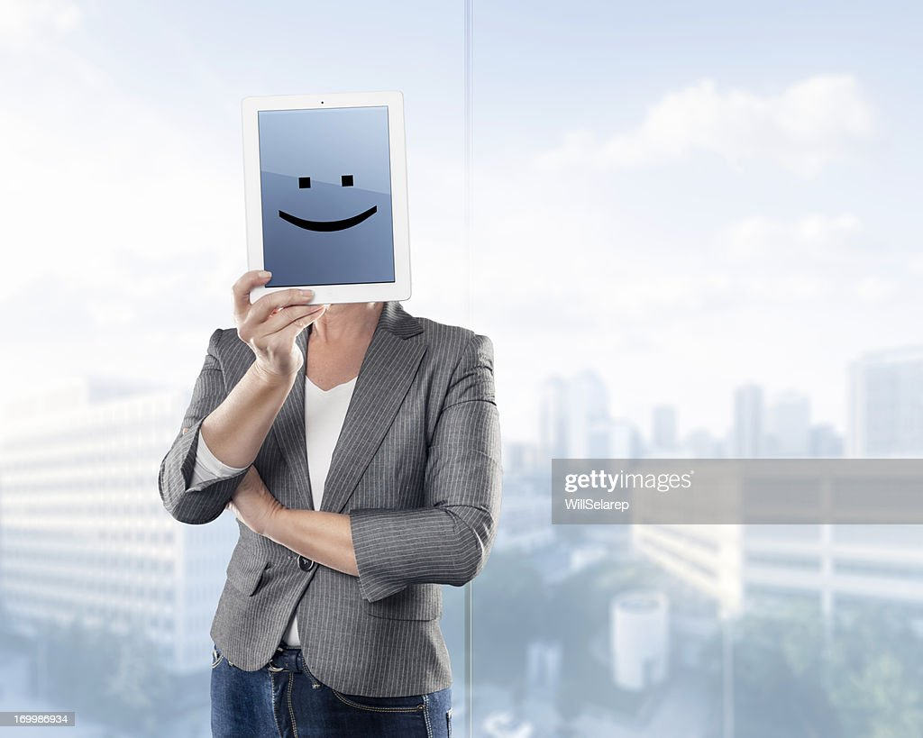 Businesswoman keeping a digital tablet with smiling emoticon