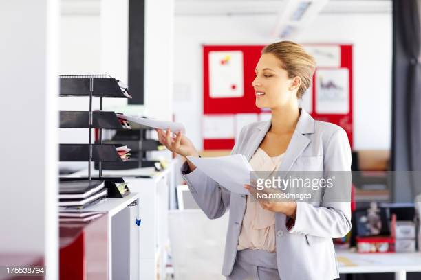 Businesswoman Keeping Documents In Paper Tray