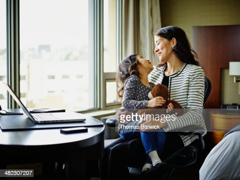 Businesswoman laughing with daughter in hotel room