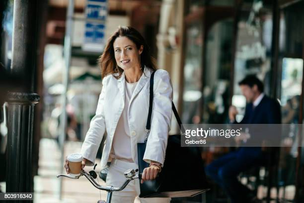 Businesswoman leading a bicycle