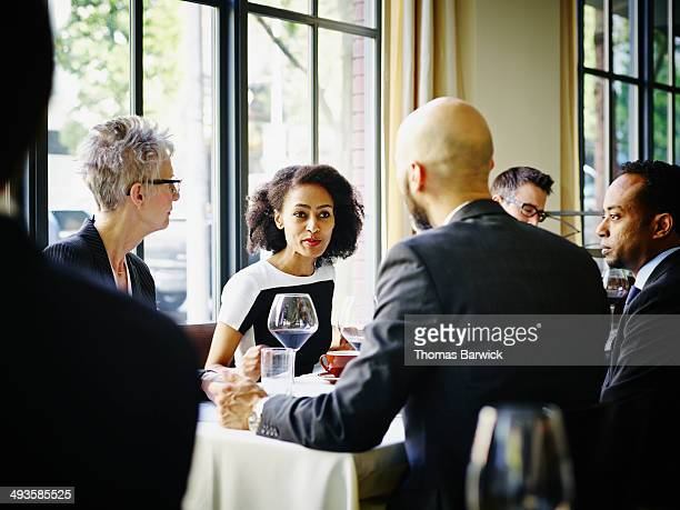 Businesswoman leading discussion at lunch meeting