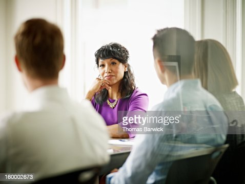 Businesswoman leading discussion with coworkers : Stock Photo