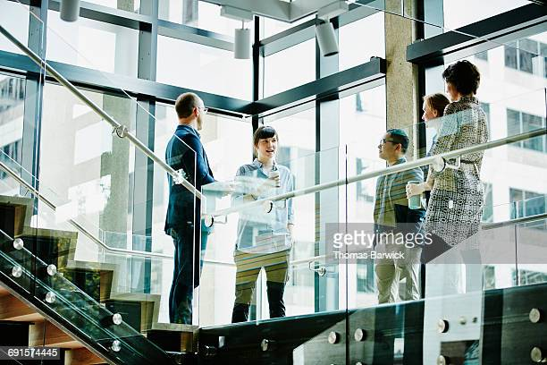 Businesswoman leading meeting on office stairs