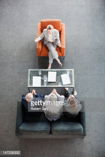 Businesswoman leading meeting with co-workers in lobby