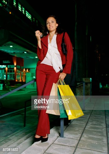 businesswoman leaning against a pole holding shopping bags