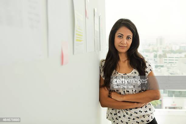 Businesswoman leaning against office wall