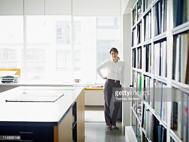 Businesswoman leaning against wall in office