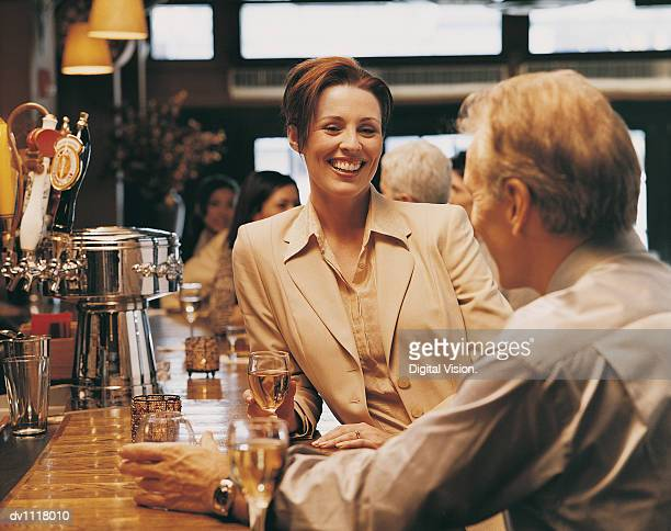 Businesswoman Leaning on a Bar Counter Smiling and Talking With a Male Colleague