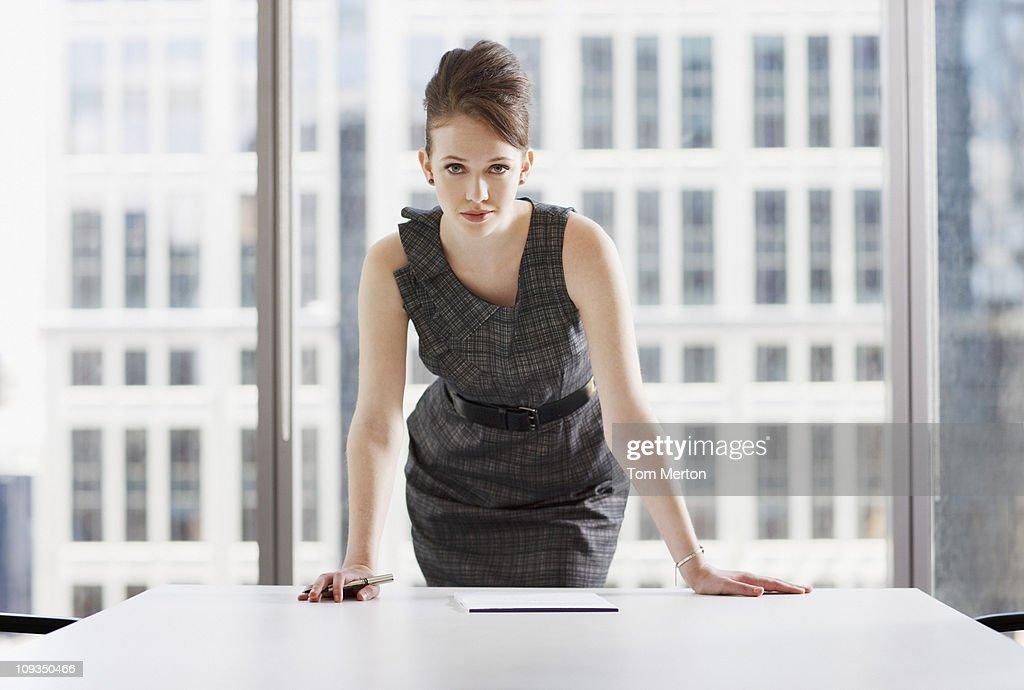 Businesswoman leaning on desk in office