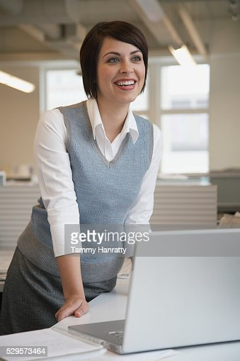 Businesswoman leaning on desk : Stock Photo