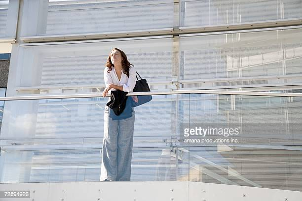 Businesswoman leaning on railing (low angle view)