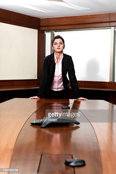 Businesswoman leaning on the conference table