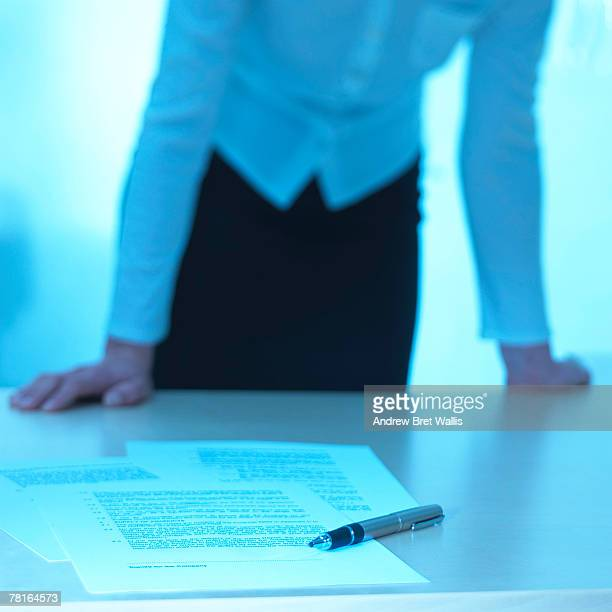 Businesswoman leaning over desk