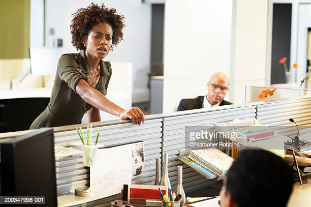 Businesswoman leaning over partition in office, looking at colleague