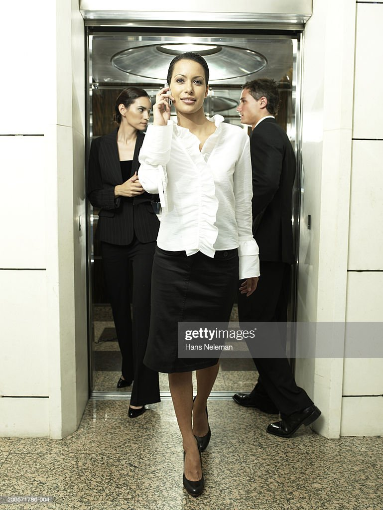 Businesswoman leaving elevator using cell phone : Stock Photo