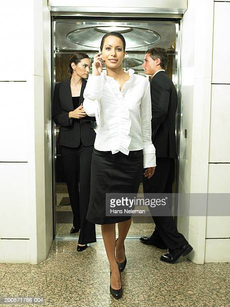 Businesswoman leaving elevator using cell phone