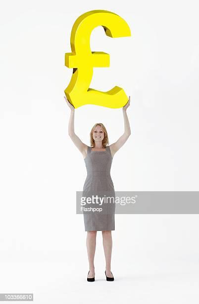 Businesswoman lifting large Pound symbol