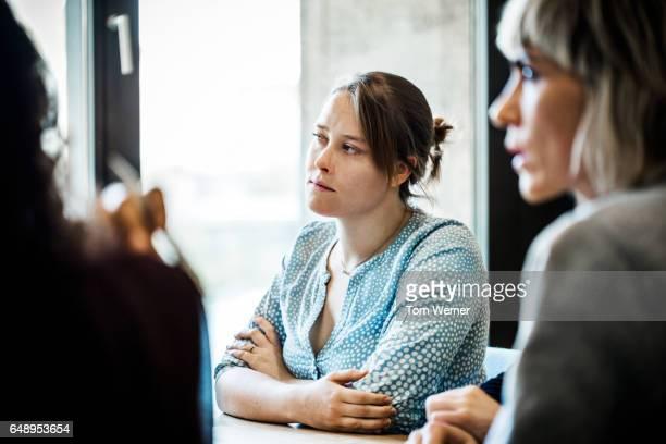 Businesswoman listening during informal team meeting