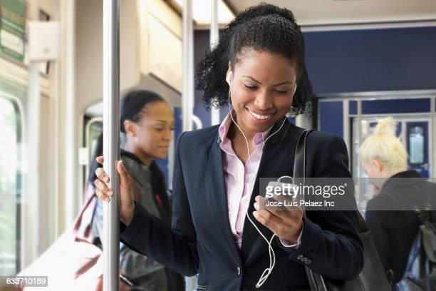 Businesswoman listening to earphones on train