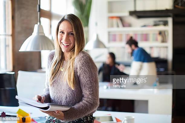 Donna d'affari che guarda e sorride alla macchina fotografica in ufficio di piccole dimensioni.