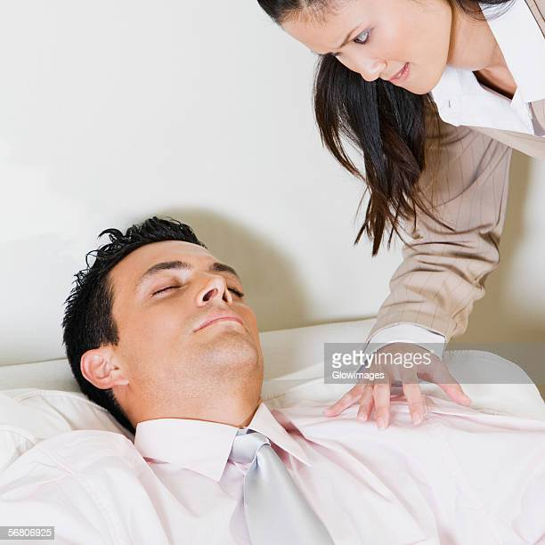 Businesswoman looking at a businessman sleeping in an armchair