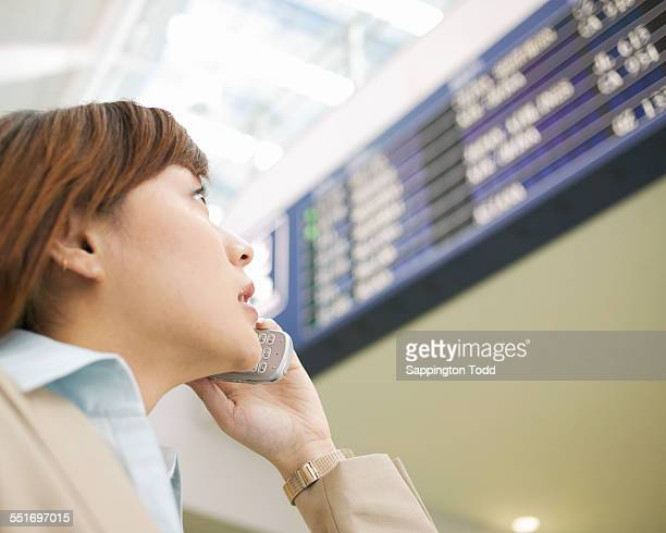 Businesswoman Looking At Arrival Departure Board